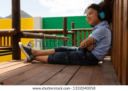 Side view of a mixed-race schoolgirl listening music on headphones while sitting in the school playg Stock photo © wavebreak_media