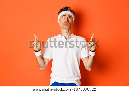 Gloomy, disappointed handsome bearded guy in activewear feeling upset, pointing up, frowning as show Stock photo © benzoix