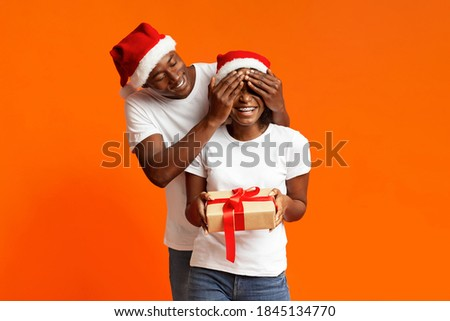 a man gives his beloved woman a gift on new years eve the man is dressed in an elegant suit and t stock photo © elenabatkova