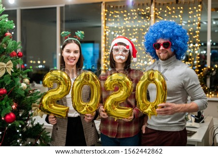 Three cheerful colleagues holding inflatable numbers by Christmas tree Stock photo © pressmaster