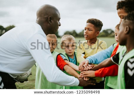 Coach coaching soccer kids soccer team. Youth sports coach using tactics board. Trainer explaining m Stock photo © matimix
