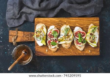 Bruschetta and Crostini with pear, ricotta cheese, honey, figs. Stock photo © Illia