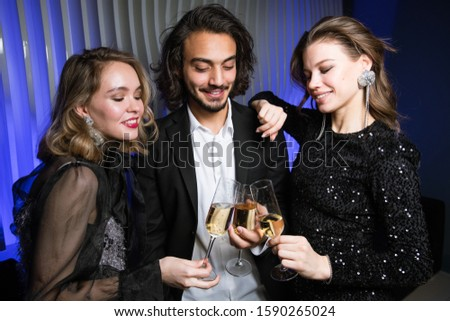 Three happy well-dressed friends toasting with flutes of champagne in night club Stock photo © pressmaster
