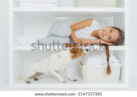 Photo of lovely preschooler lies on white shelf in washing room, has long pigtail, plays with dog, w Stock photo © vkstudio