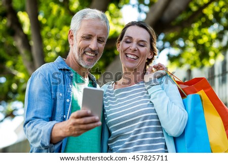 Front view of caucasian woman using mobile phone while friends interacting on beach  Stock photo © wavebreak_media
