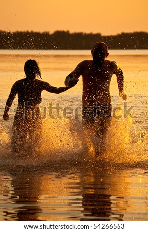 Front view of happy young Caucasian couple running at beach on sunny day. They are smiling Stock photo © wavebreak_media