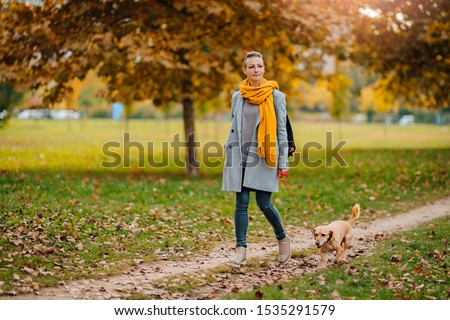 A woman walks in autumn in a public Park in a warm knitted hat and a red scarf Stock photo © ElenaBatkova