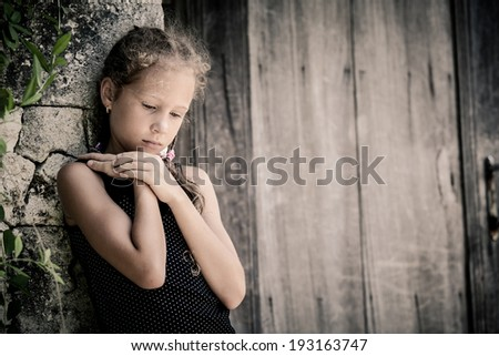 Portrait of sad little girl standing near wall in the day time Stock photo © Lopolo