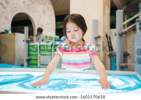 Cute little girl of Asian ethnicity making picture of blue sand by her hands Stock photo © pressmaster