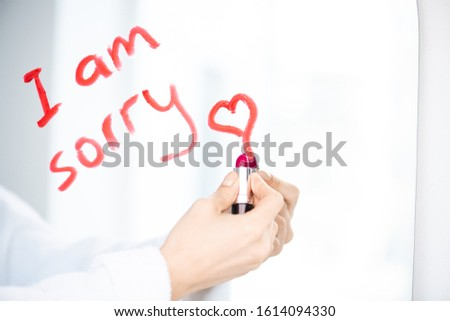 Hand of young woman writing message of sorrow with red lipstick on mirror Stock photo © pressmaster