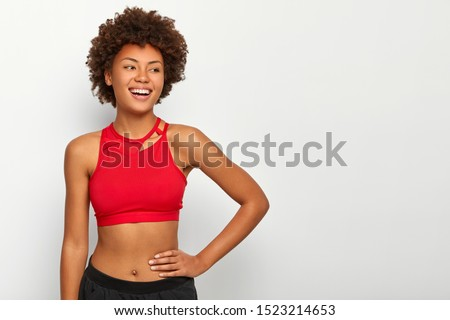 Motivated cheerful red haired female in sports bra and trousers, keeps hand in pocket, wears sneaker Stock photo © vkstudio