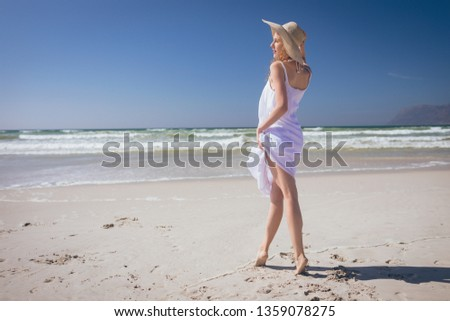 Rear view of beautiful Caucasian woman giving pose while standing at beach on a sunny day. She wears Stock photo © wavebreak_media