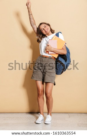 Image of delighted teen girl carrying backpack holding exercise  Stock photo © deandrobot