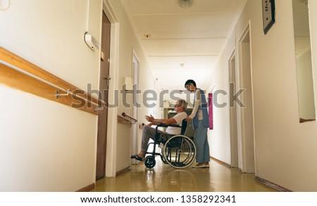 Side view of  Asian female nurse pushing disabled Caucasian senior male patient sitting in wheelchai Stock photo © wavebreak_media