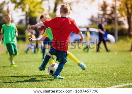 School boys playing football game. Young players kicking soccer  Stock photo © matimix