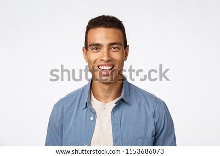 Cheerful, friendly handsome young tanned man in blue shirt over t-shirt, laughing, smiling happy as  Stock photo © benzoix