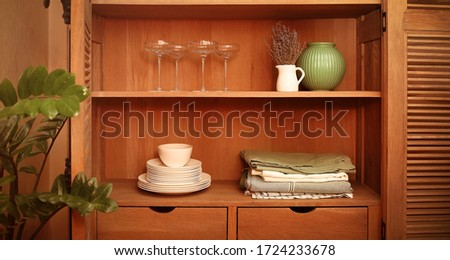 Kitchen cupboard with disheslike plates, tableclothes and glasse Stock photo © dashapetrenko