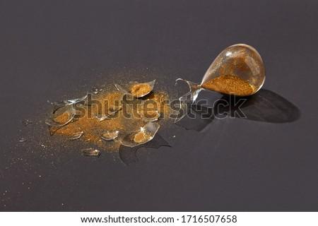 Broken antique sandglass with golden sand on a black duotone background. Stock photo © artjazz