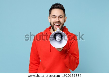Image of happy unshaven man in sweatshirt screaming with clenchi Stock photo © deandrobot