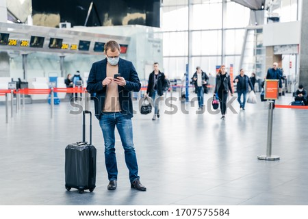 Foto stock: Horizontal Shot Of Man Poses In Crowded Airport Uses Cell Phone Checks Time Of Flight Online Stan