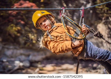 Brave little boy rappelling high among the trees in an Adventure Park for children. Extreme kid. The Stock photo © galitskaya