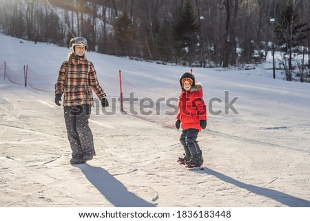 Mother teaches son snowboarding. Activities for children in winter. Children's winter sport. Lifesty Stock photo © galitskaya