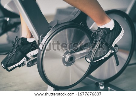 Fitness machine at home woman biking on indoor stationary bike exercise indoors for cardio workout.  Stock photo © Maridav
