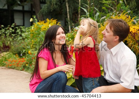 Parents observe as their daughter in red dress blows soap bubbles in summer garden. stock photo © Paha_L