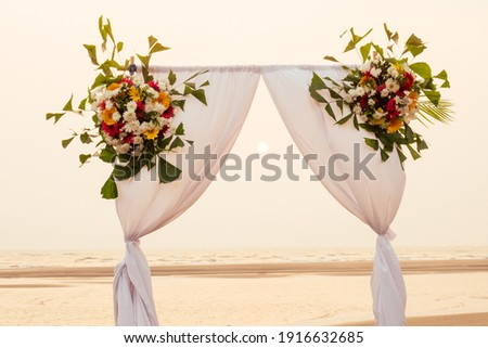 Sunset. Wedding ceremony arch with flowers decorative arrangemen Stock photo © Victoria_Andreas