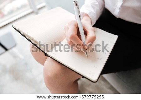 Cropped photo of young incredible business woman writing notes Stock photo © deandrobot