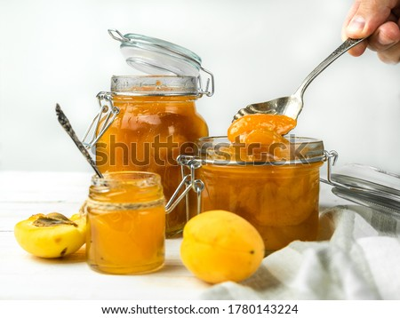 apricot jam in a jar and fresh fruits with leaves on white wooden table breakfast stock photo © yelenayemchuk