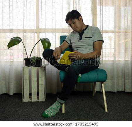 若い男 読む 図書 座って 椅子 リビングルーム ストックフォト © TeoLazarev