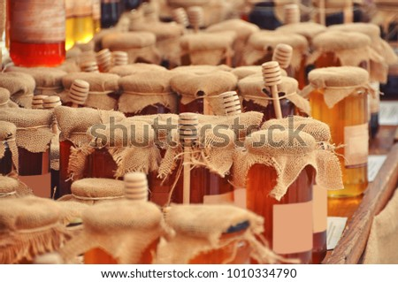 Jars and honey sticks with natural honey on shelf in shop. Sale of natural honey in market Stock photo © FreeProd