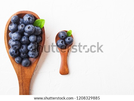 Fresh raw organic blueberries with leaf on large and mini wooden spoon on white background. Food con Stock photo © DenisMArt