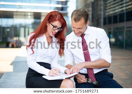 Businesswoman writes in agenda and businessman sitting by her Stock photo © boggy
