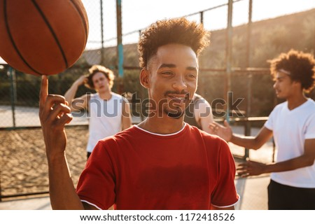 portrait of caucasian muscular guy spinning ball on his finger stock photo © deandrobot