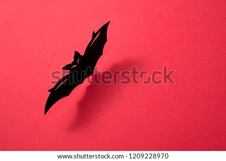 Paper flying handcraft bat presented on a red background with a pattern of shadows and space for tex Stock photo © artjazz