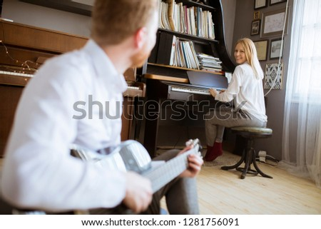Stock photo: Man playing acoustic guitar with young beautiful woman who plays