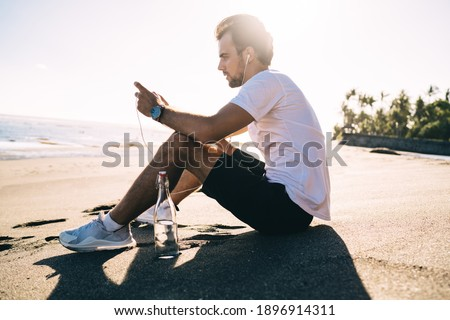 Sports man outdoors on the beach sitting near bottle with water on rug. Stock photo © deandrobot