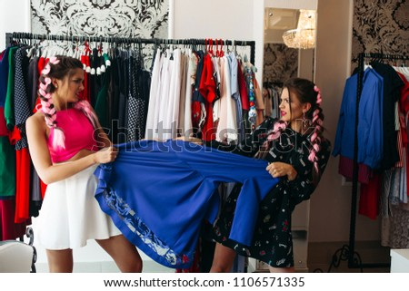 Two young emotional and stylish woman pulling clothes and arguing for it. Action in fitting room aga Stock photo © studiolucky