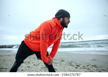 handsome young sports man standing on the beach listening music with earphones make stretching exerc stock photo © deandrobot
