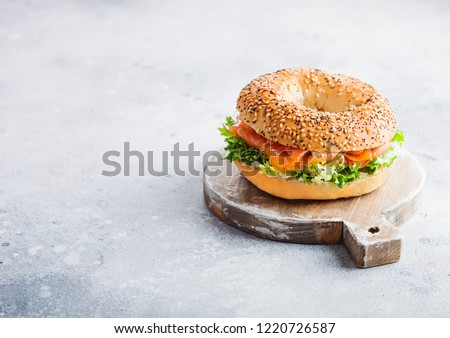 fresh healthy bagel sandwich with salmon ricotta and glass of milk on light kitchen table backgroun stock photo © denismart