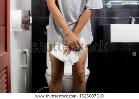 Man Holding Tissue Paper Roll Standing In Front Of Toilet Bowl Stock photo © AndreyPopov