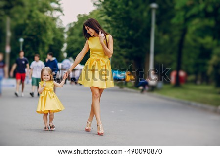 beautiful young mother with small daughter walks through city stock photo © elenabatkova