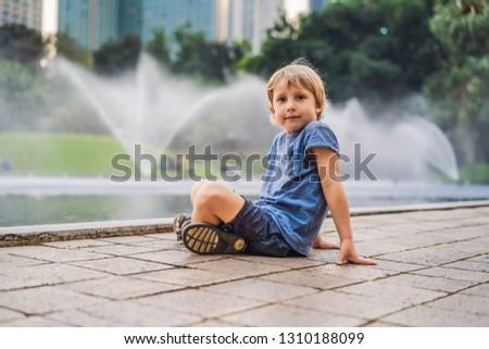 Boy on background of Fountain on the lake in the evening, near b Stock photo © galitskaya