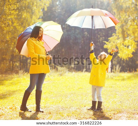 mother and child on a rainy day in a park with umbrella Stock photo © Lopolo