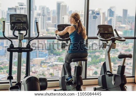 Young woman on a stationary bike in a gym on a big city background VERTICAL FORMAT for Instagram mob Stock photo © galitskaya