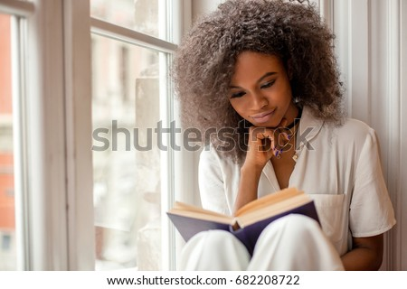 smiling young woman reading the book and sitting on the grass in Stock photo © Freedomz