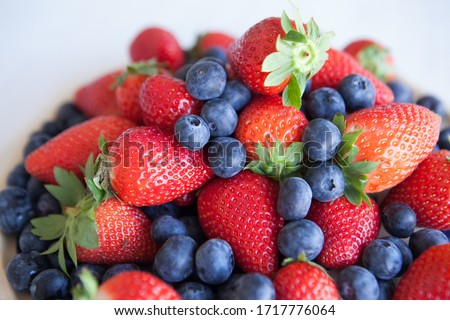 fresh organic summer berries mix in white plate on blue kitchen table background raspberries straw stock photo © denismart