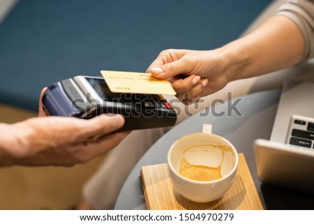 female hand holding plastic card over electronic payment machine held by waiter stock photo © pressmaster